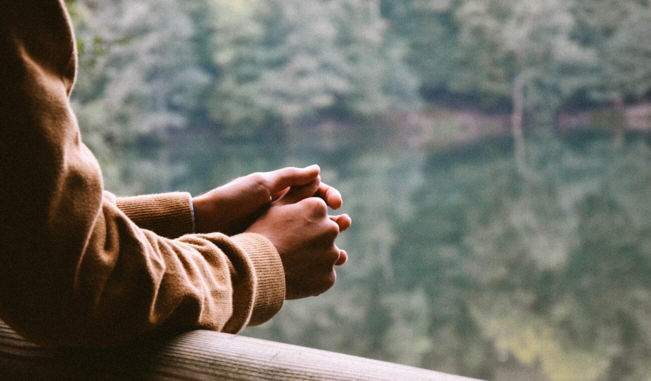 Man standing looking at lake